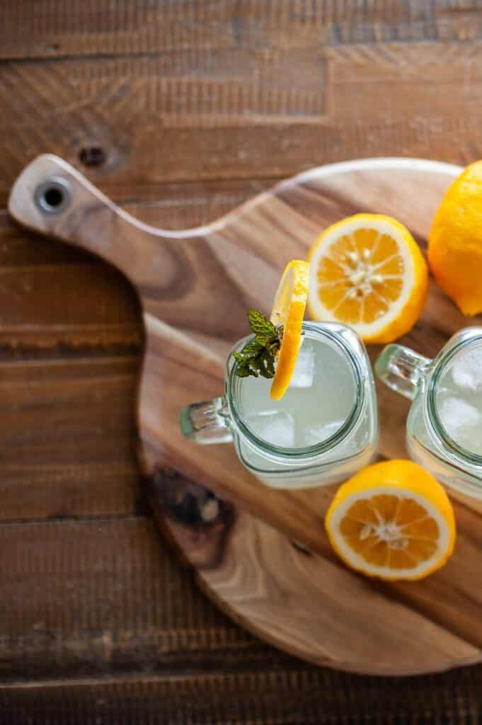 top view of a wooden platter containing glasses of lemonade and slices of lemon