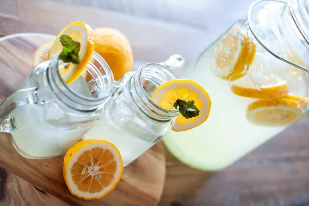 side view of glasses and pitcher of lemonade with lemon slices