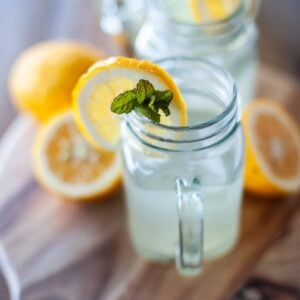close up of a glass mug containing lemonade with a slice of lemon on the side
