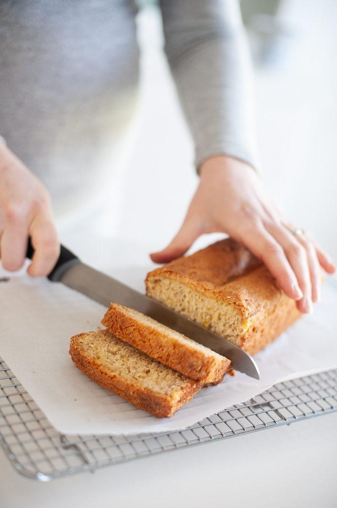 a person slicing banana bread