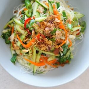 top view of noodle salad in a white bowl topped with shallots and herbs