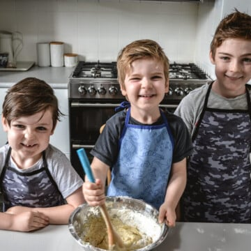 three boys standing at a bench, cooking and smiling