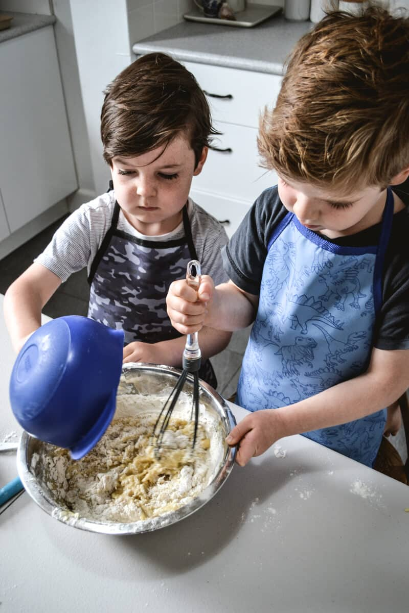 two boys mixing cake batter in a large bowl