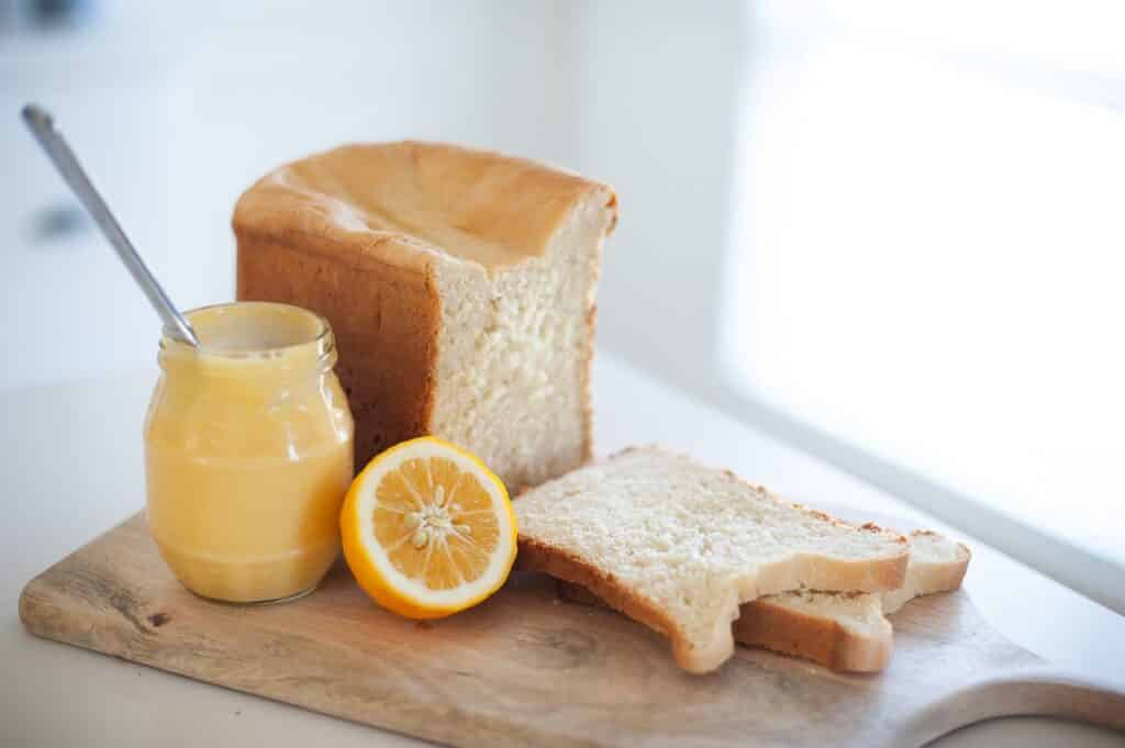 a-loaf-of-bread-on-a-wooden-board-with-lemon-spread