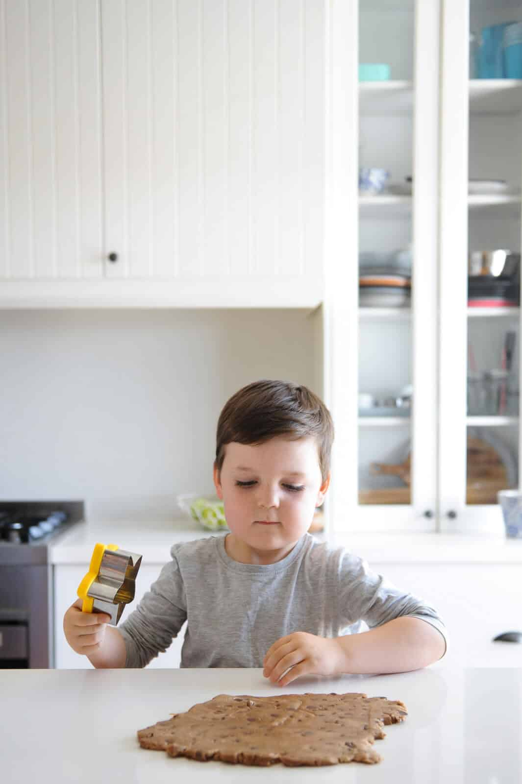 a young boy cooking at a kitchen bench
