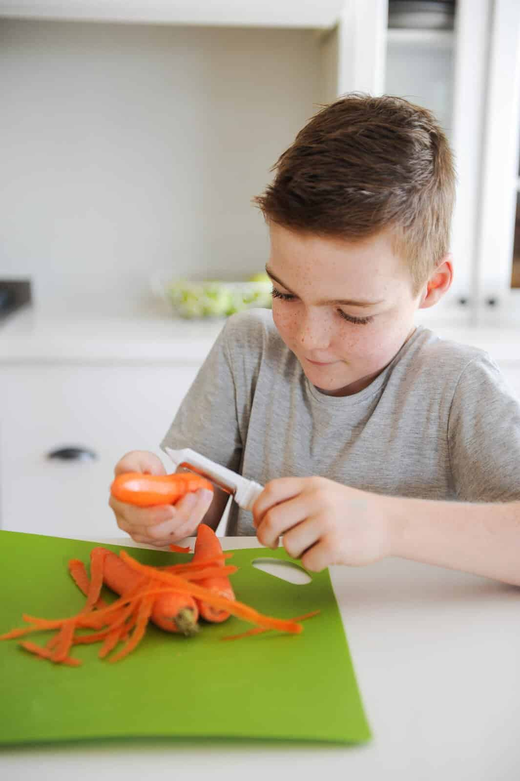 a young boy slicing carrots in a kitchen