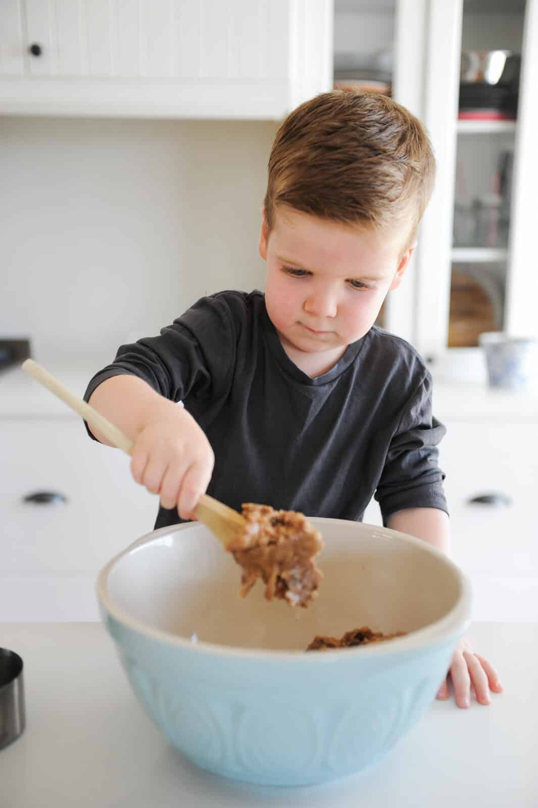 close up of child stirring dough in a bowl
