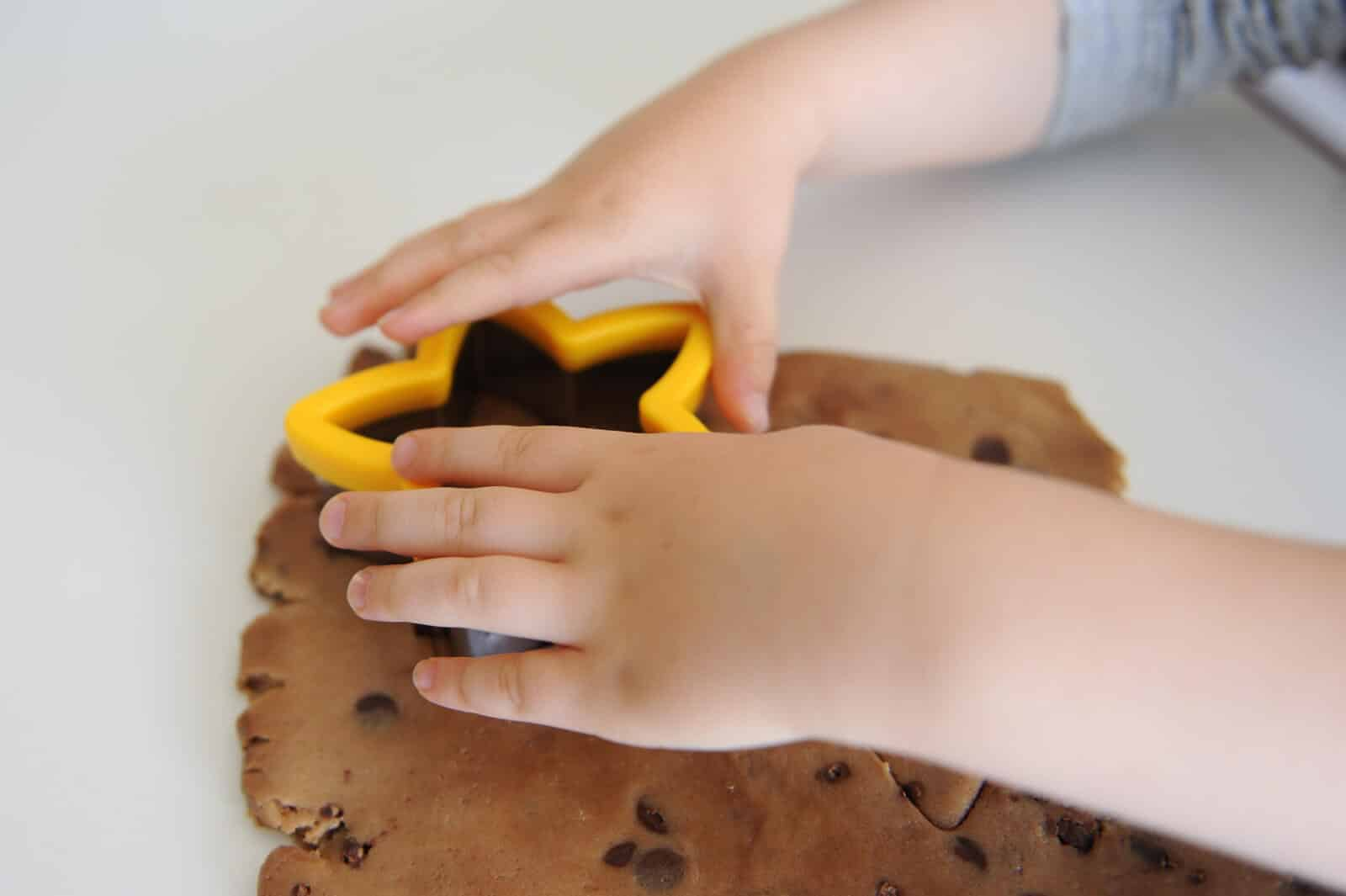 child\'s hands cutting dough with a star cutter
