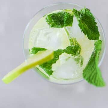 top view of a mojito with sprigs of mint and lime slice