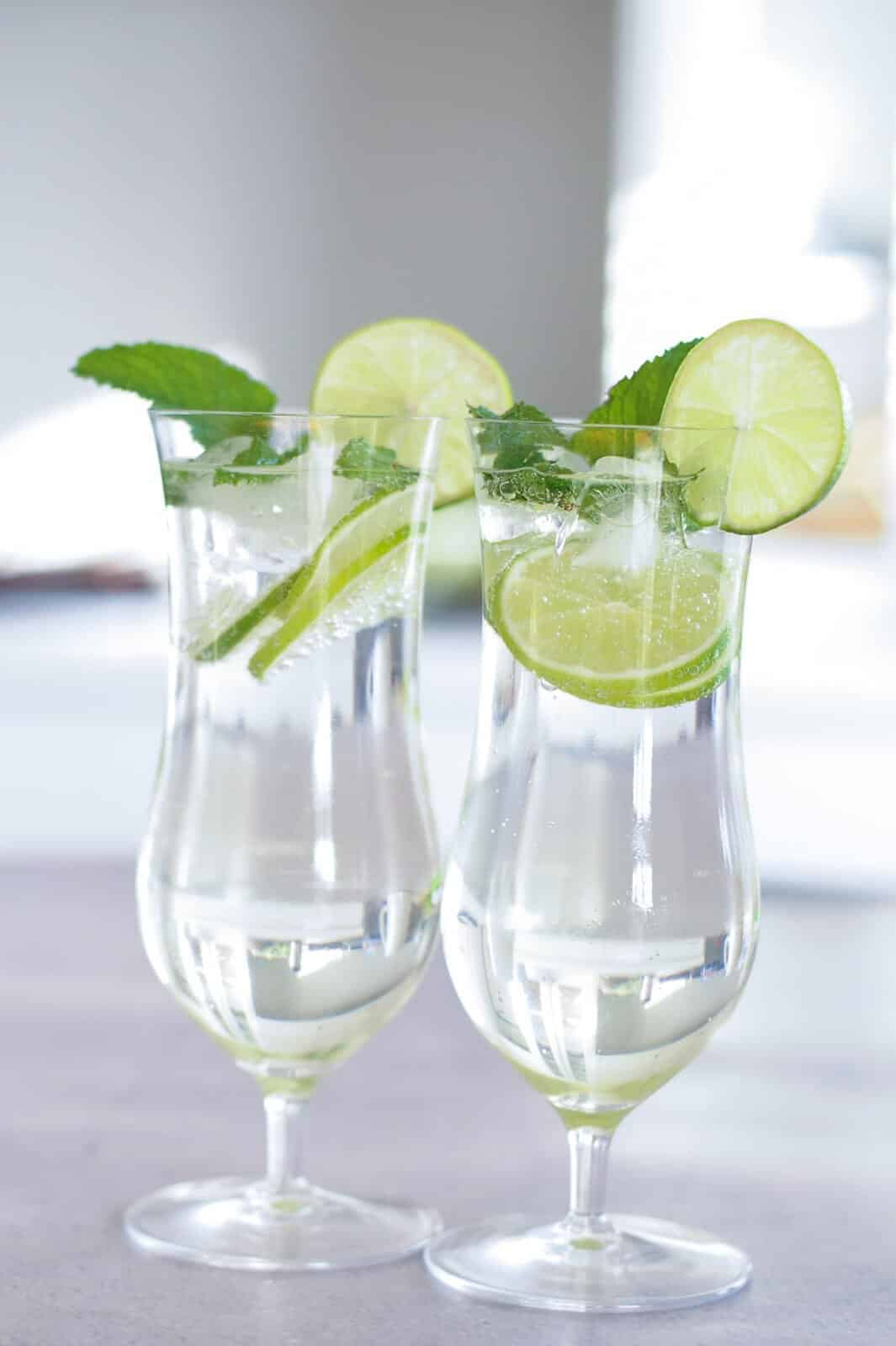 A table with wine glasses, with lime and mint