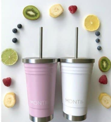 close up of a pink and white smoothie cup surrounded by fruit