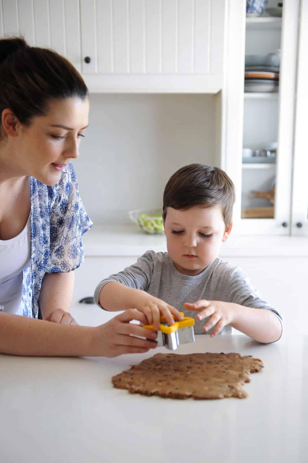 A young boy cutting cookie dough