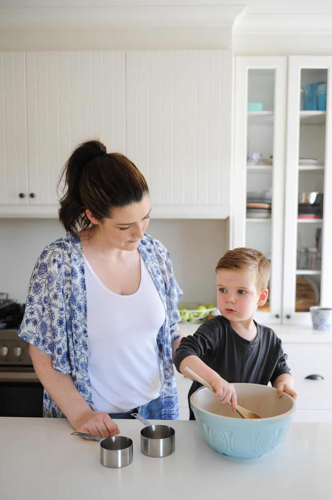 close up of mother and child cooking in a kitchen