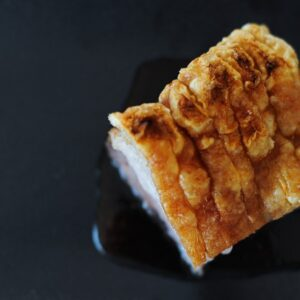 top view of pork belly with crispy crackle on black plate