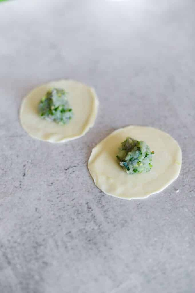 top view of gyoza wrappers with green prawn filling in centre