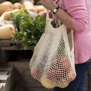 A person in a pink top holding food, with a cotton bag slung over their shoulder