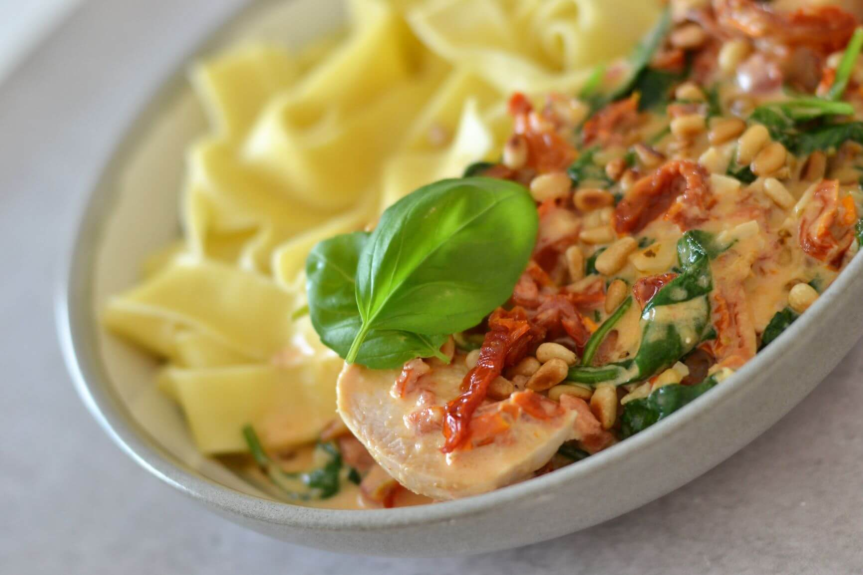 side view of bowl containing chicken, pasta and fresh green herbs