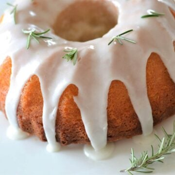 a close up of a bundt cake with white icing and rosemary sprigs