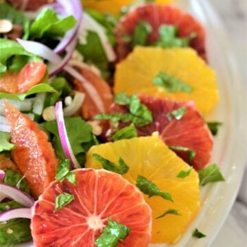 slices of red and yellow oranges on a white plate with salad