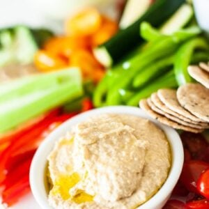 side view of hummus on a platter with chopped vegetables