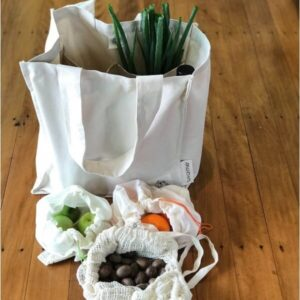 different cloth bags containing food on wooden floor