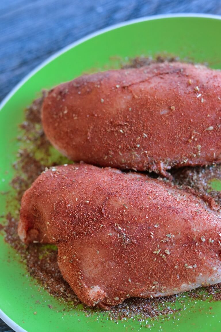 two chicken breasts on a green plate with spices