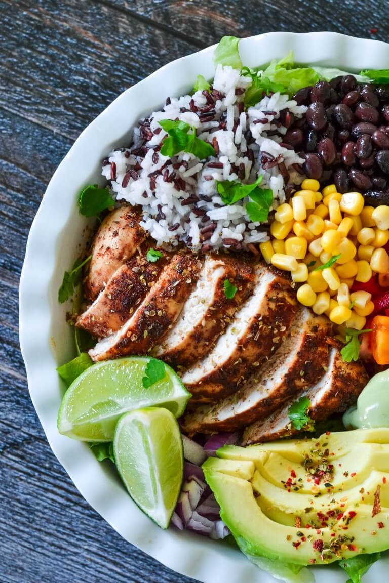 top view of a white bowl with sliced chicken, corn and lime wedges