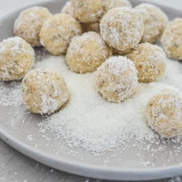 finished bliss balls in coconut on grey plate
