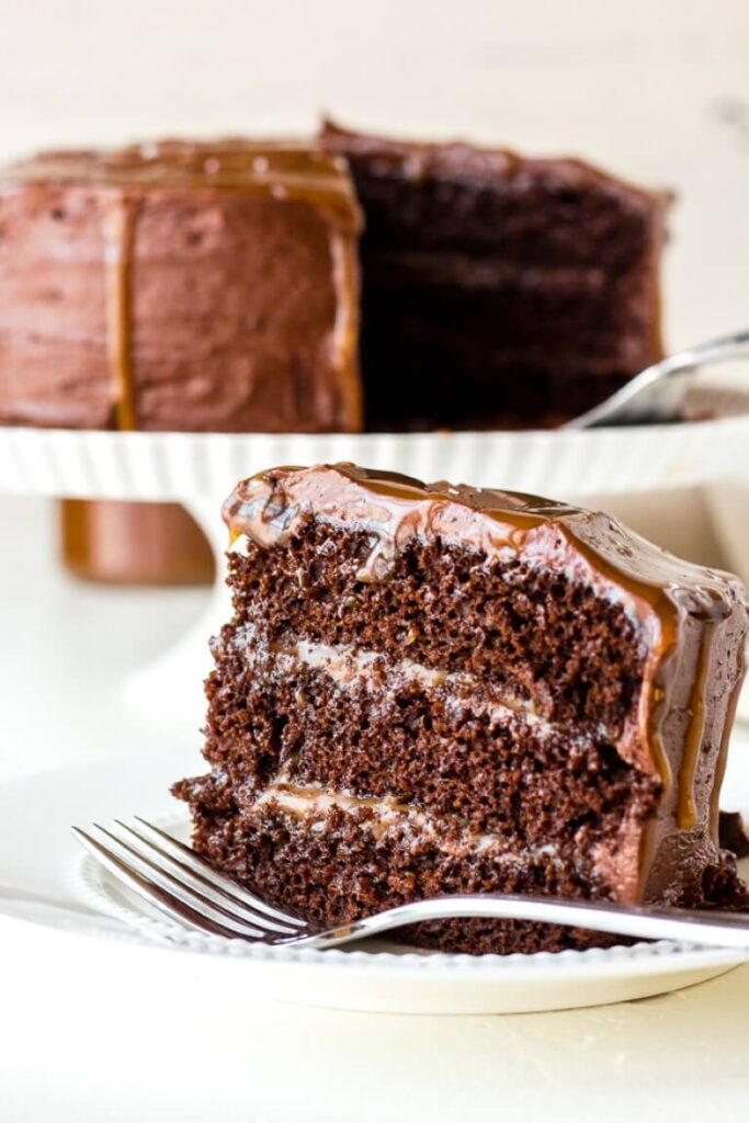 close up of chocolate layered cake on a plate with a fork