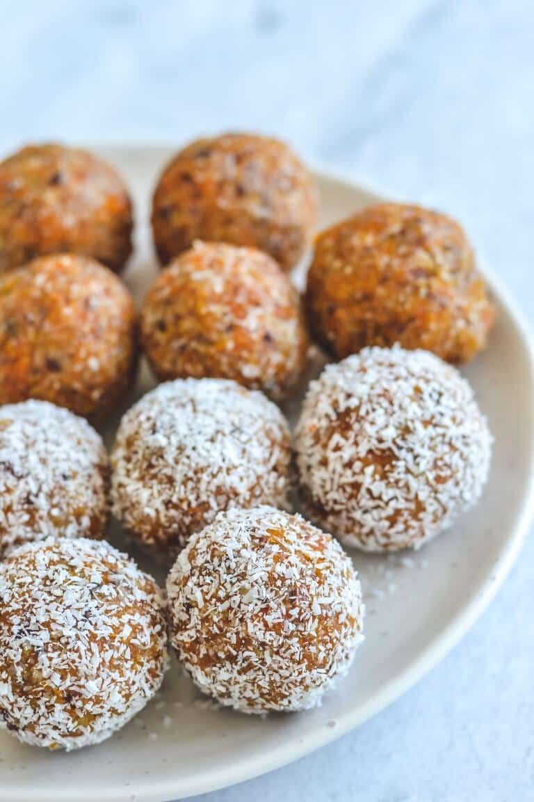 apricot bliss balls coated in coconut arranged on a white plate