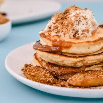 pancakes stacked on a white plate with banana on the side