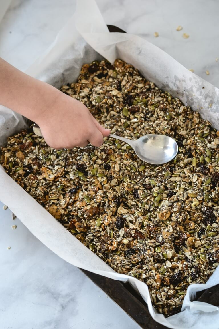 a hand holding a spoon and pressing granola into a tray lined with paper