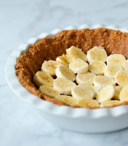 slices of banana arranged on biscuit base in white pie dish