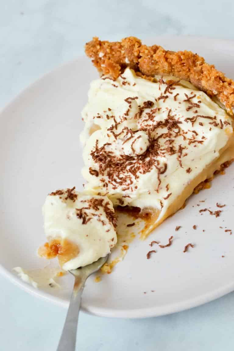 slice of banoffee pie on white plate with chocolate shavings