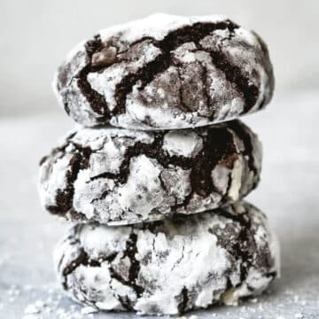 three chocolate crinkle cookies stacked on top of each other, coated in icing sugar
