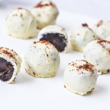 chocolate truffles with white chocolate and oreo crumbs on white bench