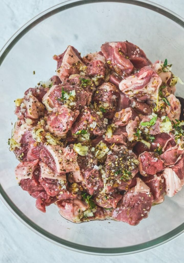 top view of a glass bowl containing lamb pieces and herbs