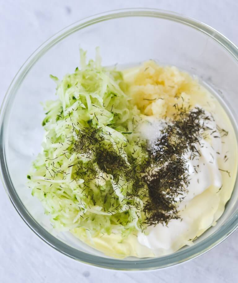 A bowl containing yoghurt, cucumber and herbs