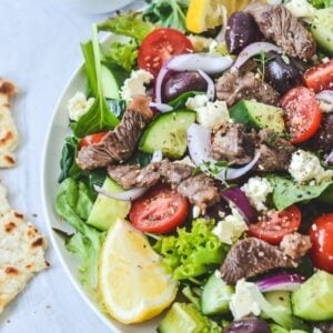 A plate of salad on a white plate, with lamb and lemon wedges