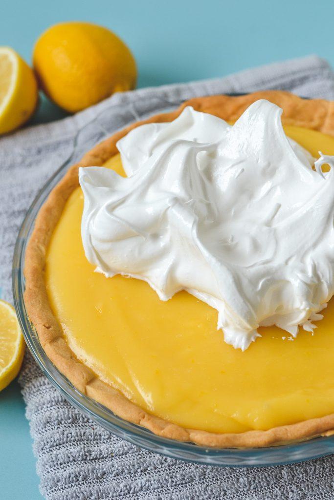 meringue being added to lemon curd pie