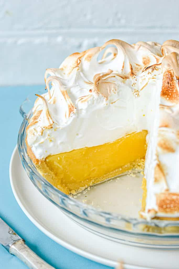 lemon meringue pie in glass dish, with piece missing