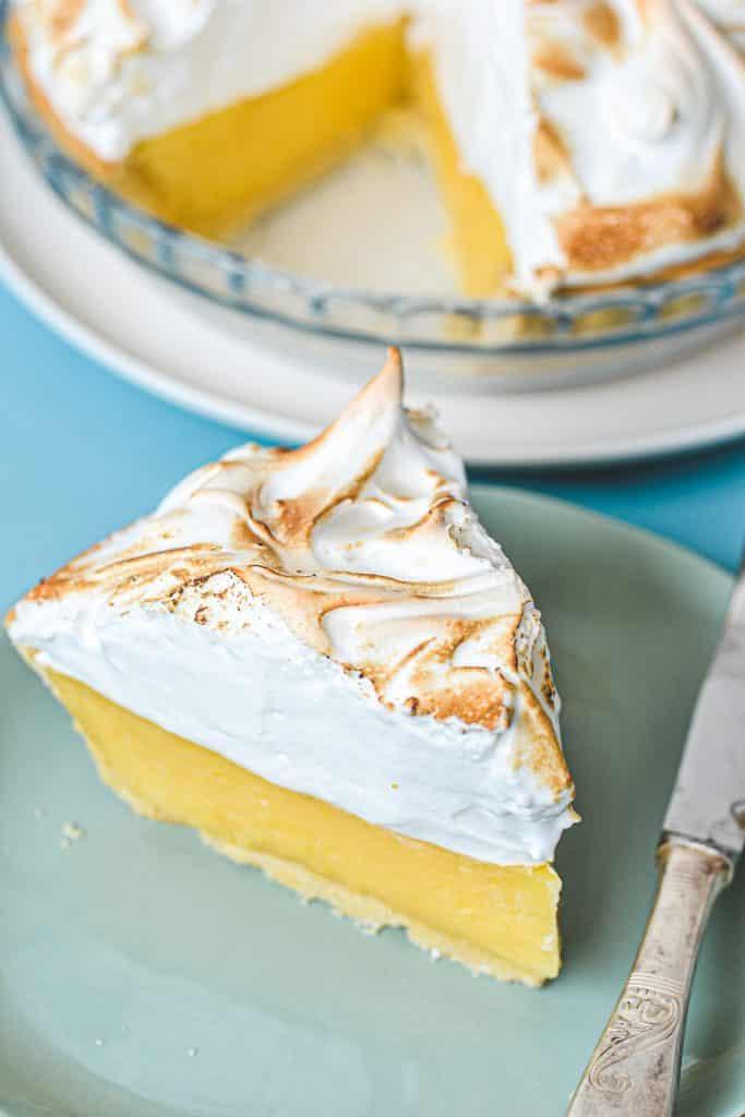 lemon meringue pie slice on green plate with pie in background