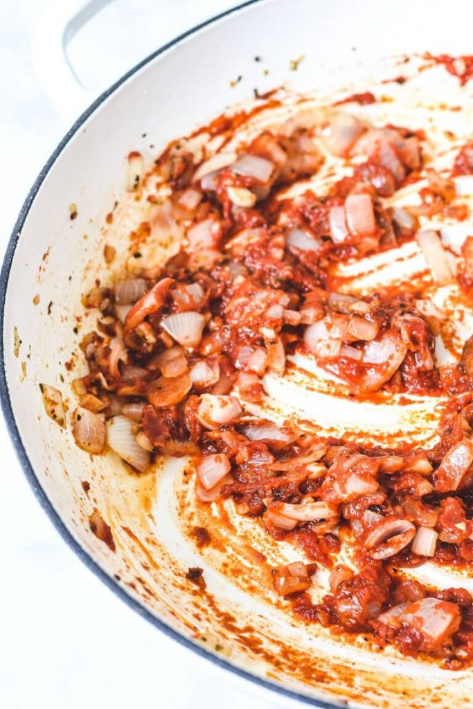 tomato paste, onion and garlic in a white pan