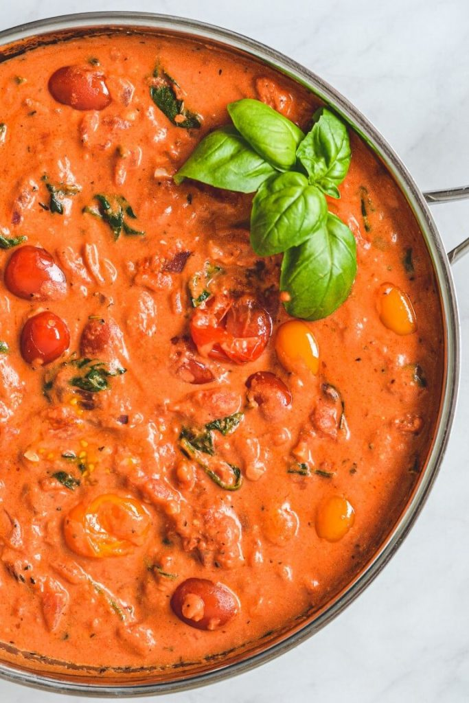 top view of pasta sauce in a pan with tomato and herbs