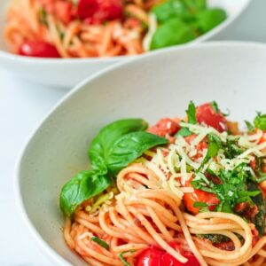 finished pasta and sauce in white bowl with herbs