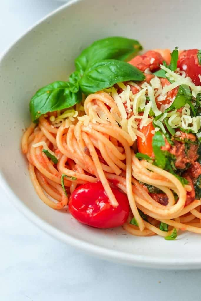 tomato pasta in white bowl with herbs and cheese
