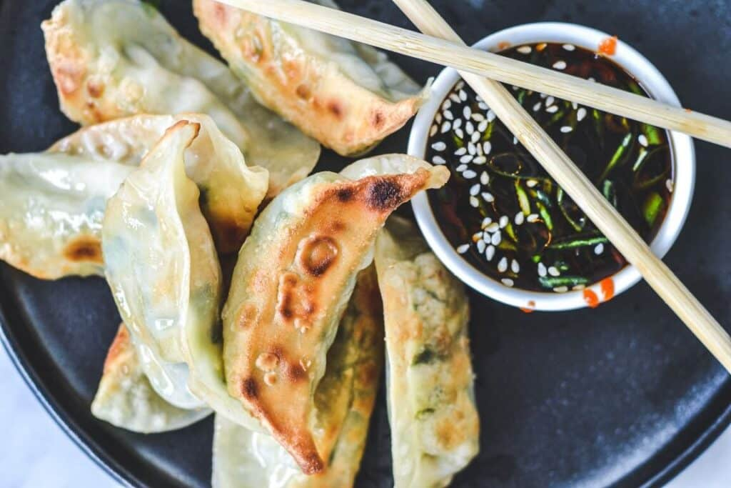 top view of dumplings with chopsticks and dipping sauce