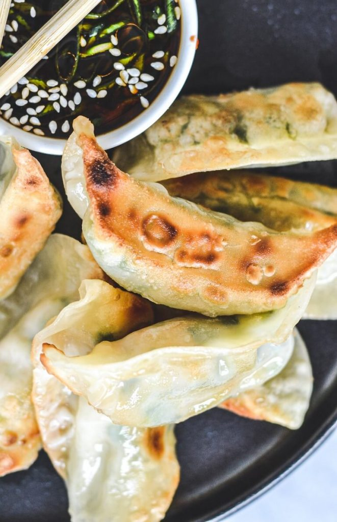 A close up of a plate of food, with gyoza with crispy edges