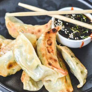 dumplings arranged on black plate with chopsticks