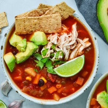 top view of Mexican soup with corn and chicken and a lime wedge